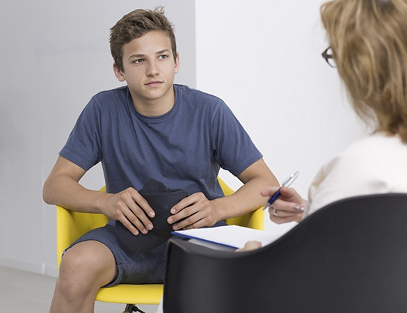 Teenage boy in therapy session with female psychologist